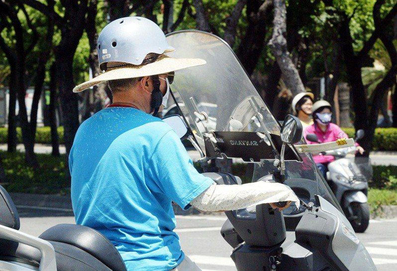 有騎士為了防曬,在安全帽裡面先戴上斗笠遮陽,在官員眼裡是不合格的作法。圖/聯合報系資料照片