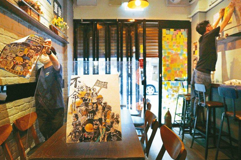 港版國安法已在香港生效,香港一家餐廳員工昨天拆除貼有反送中信息的貼紙和海報,以免觸及港版國安法。(美聯社)