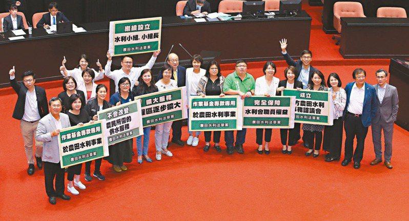 「農田水利法」三讀通過後,民進黨立委手持標語在立院合影。 記者林澔一/攝影