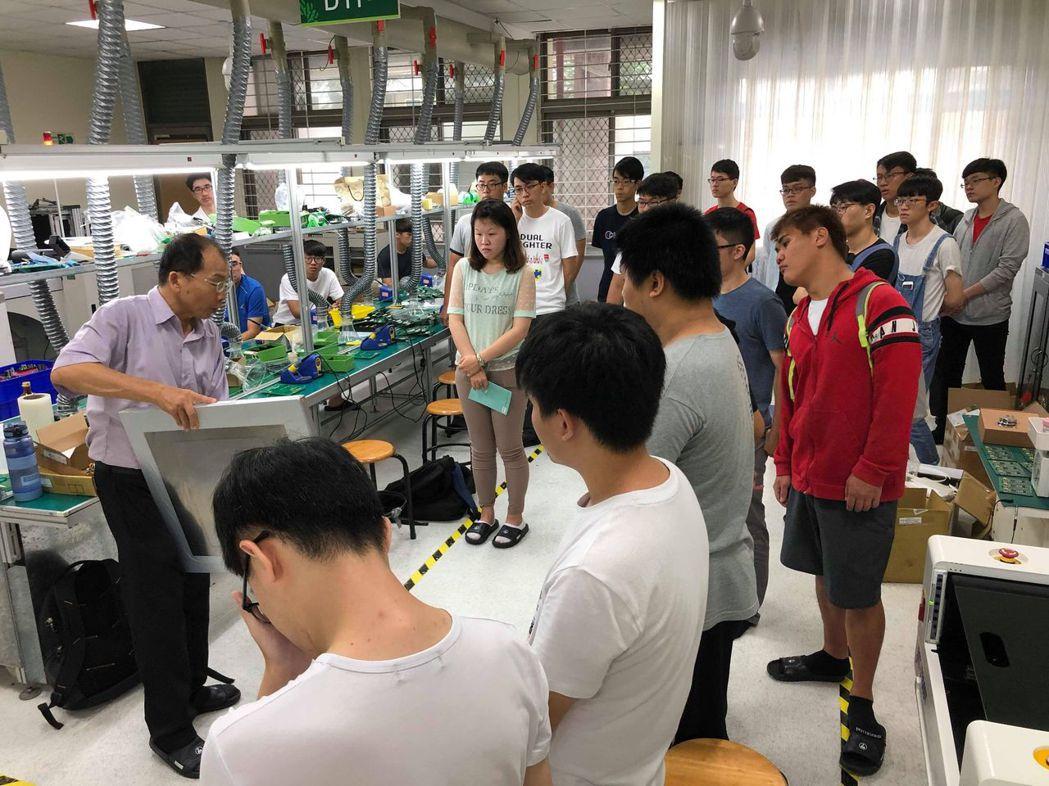 電機系主任蔡明村(左一)在太陽能組裝實務課程中賣力教導學生PCB製程。 南臺...