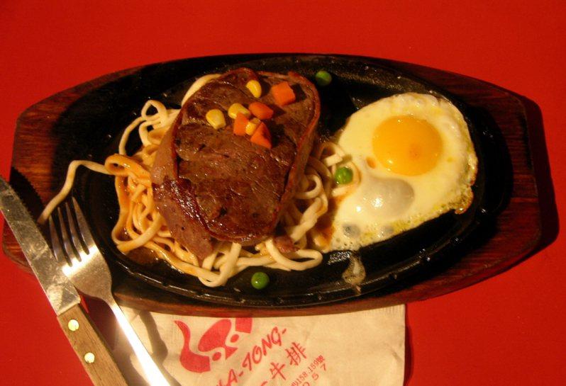 台式牛排上桌前會在鐵板上打顆蛋,利用鐵板熱度煮熟。 圖/聯合報系資料照