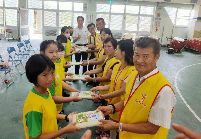 台南市官田國小校友胡朝枝(右)今天回到「唯一的母校」,捐贈幸福農場溫室智慧設備及10萬元獎助學金,學生回贈自己種植的官田米。圖/校方提供
