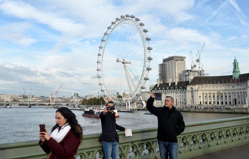 全球50多國旅客自10日起入境英國不用隔離兩周,圖為多名遊客以「倫敦眼」摩天輪為背景自拍的畫面。路透