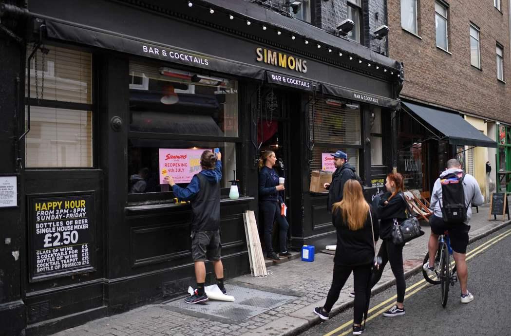一間倫敦蘇活區酒吧員工6月30日忙著在店外貼出即將重新開業的宣傳海報。法新社