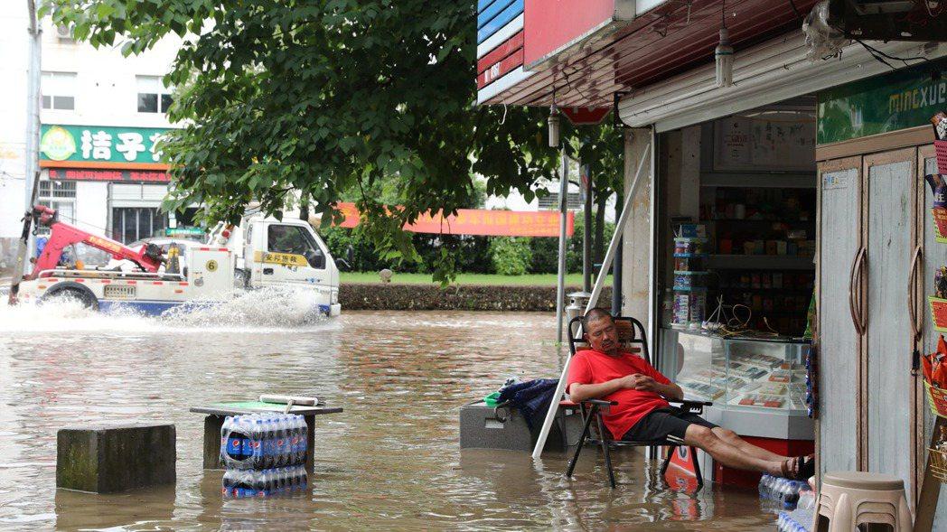 圖為浙江衢州6月30日因大雨導致路面積水,不過當地一名男子仍淡定地在自家雜貨店門...