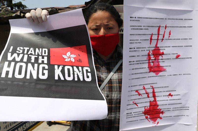 一名流亡的西藏社運人士4日在印度達蘭薩拉拿著標語,抗議港版國安法實施。 (歐新社)