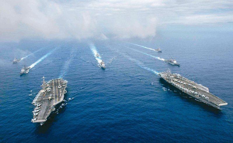 美國航空母艦雷根號和尼米茲號打擊群率領船艦和飛機,在菲律賓海展開聯合演習。(路透資料照片)
