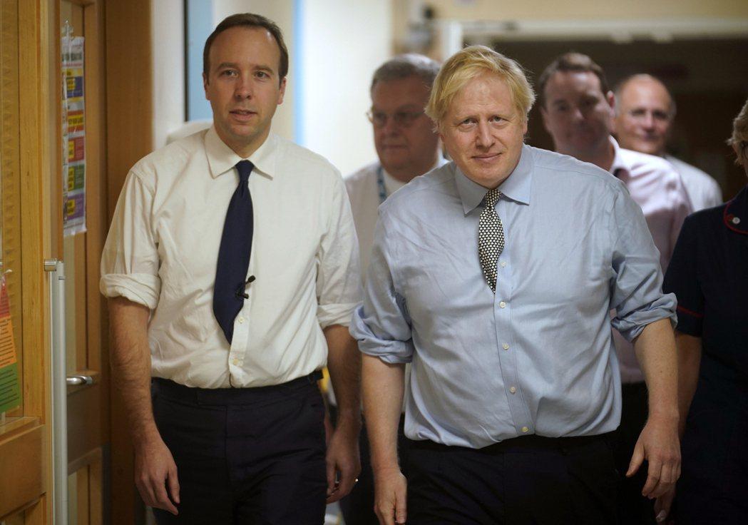 英國首相強生(右)和衛生大臣韓考克(左)2019年一同參訪一家醫院時的檔案照。 ...