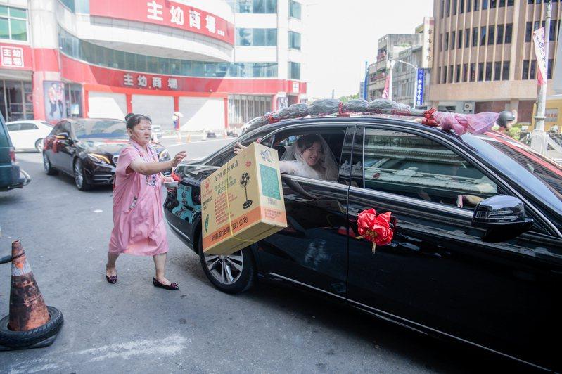 新娘吳詩于坐上禮車離家時,從車上丟下一箱「電扇」給娘家母親,這瞬間有趣畫面被攝影師精準拍下。圖/蔡睿哲(菜菜大哲)提供