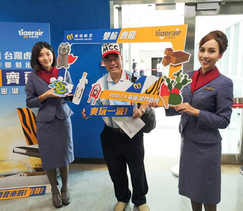 搭乘台灣虎航首航旅客開心與背板合照。圖/台灣虎航提供
