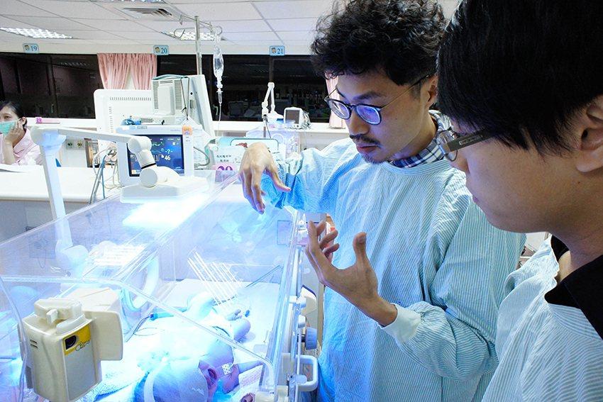 中原商設王暄文(右)為製作「小烏龜光療衣」,多次參訪新生兒診療室,諮詢專業意見。...