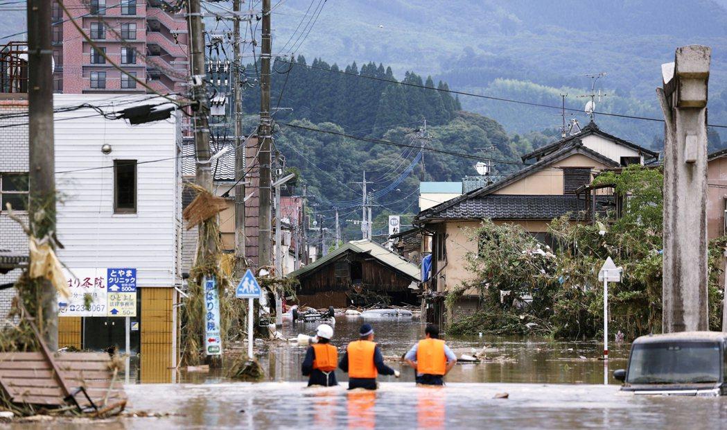 圖為日本警察在球磨川沿岸搜尋受困民眾。 圖/路透社