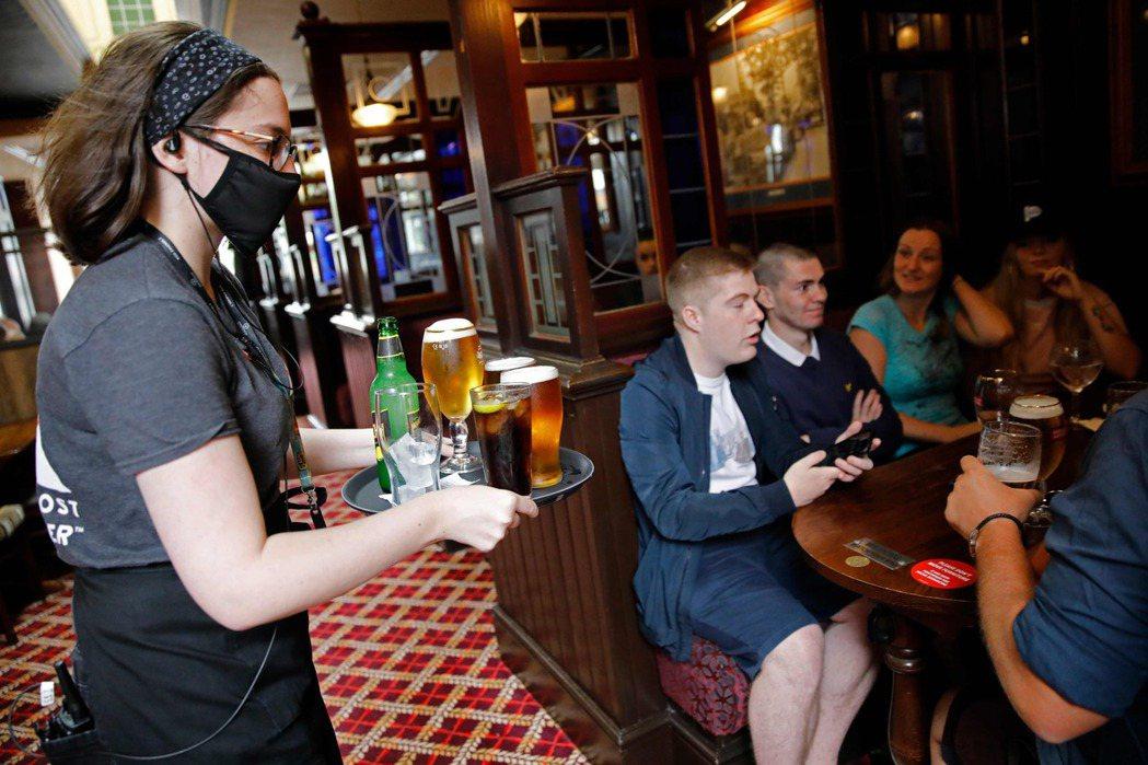 擁擠的酒吧是新冠病毒傳播的最佳地點。圖為倫敦酒吧4日重新營業。法新社