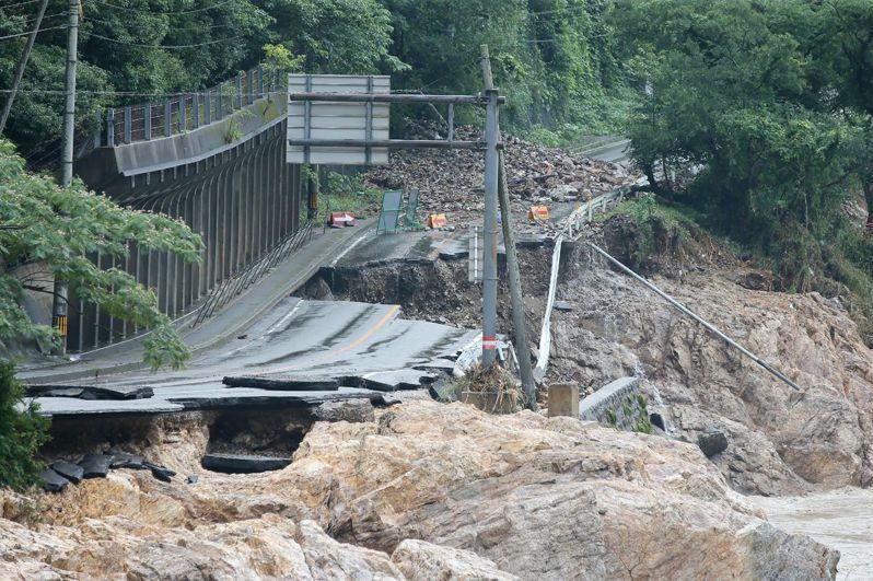 6日照片顯示,日本九州熊本縣降下破紀錄暴雨後,一條臨河道路的地基被河水掏空。(法新社)