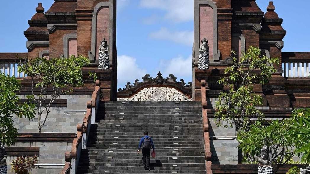 一名男子走在印尼峇里島國際機場航廈外的階梯上。 法新社