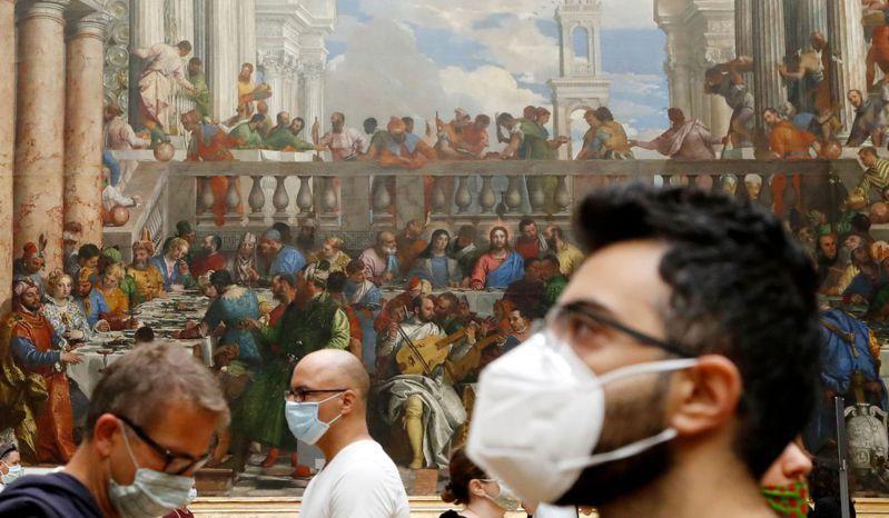 巴黎羅浮宮6日重新開放,遊客戴口罩賞畫。(法新社)