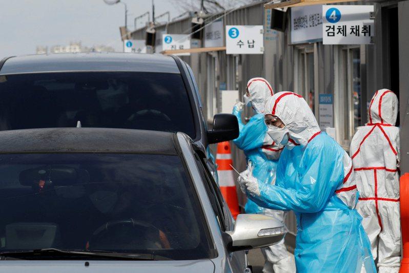 一名2019冠狀病毒疾病(COVID-19)患者接受雙肺移植手術後逐漸康復,創南韓首例。圖為南韓醫療人員在大邱市一處得來速採檢站為駕車民眾採樣。(路透)