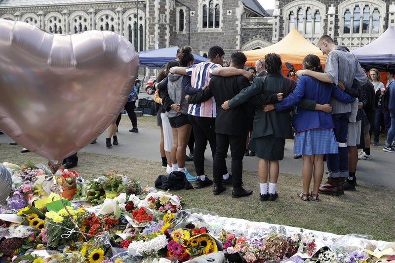 學生為屠殺事件身亡的死者祈福禱告。 圖/美聯社
