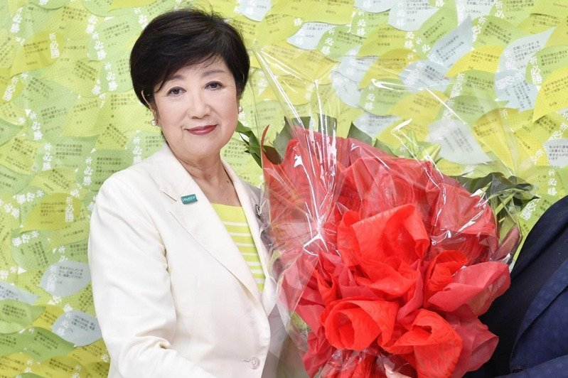 東京都知事小池百合子在贏得連任後於記者會上接受獻花。(美聯社)