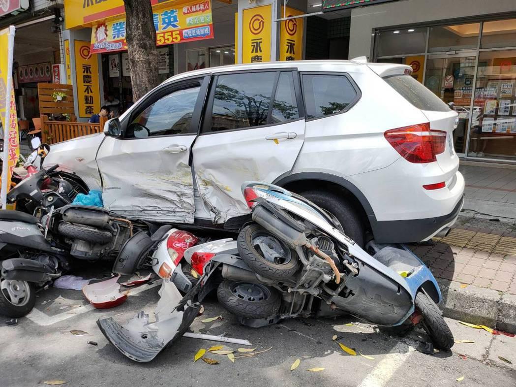 白色BMW休旅車涉接連擦撞2輛車,最後衝撞路邊整排18輛機車。記者林伯驊/翻攝