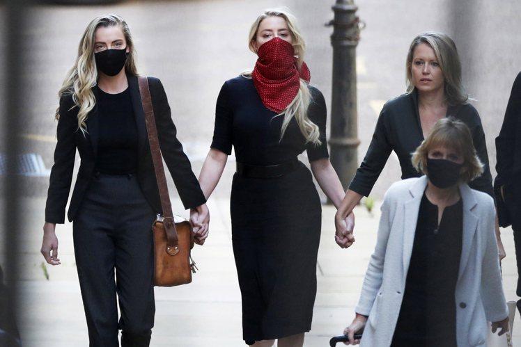 安珀赫德(中)在姊妹惠妮(左)、律師珍妮佛(右)的陪同下出庭。(歐新社)