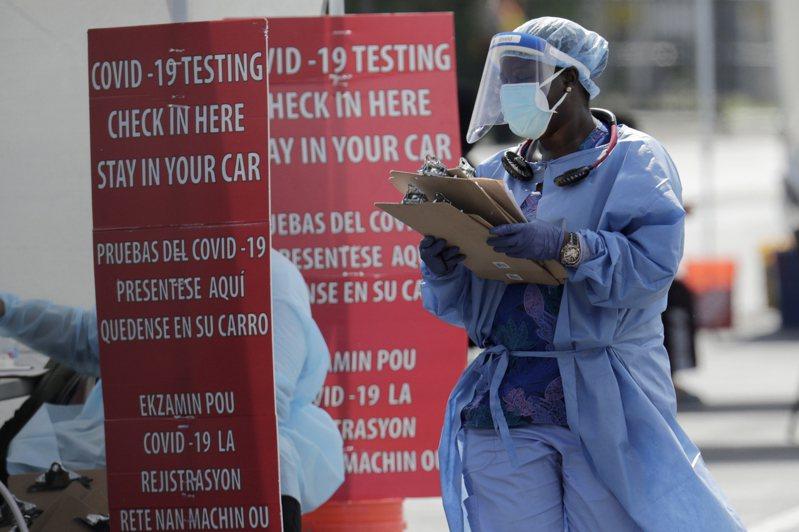 佛州單日新增1萬5299起新冠肺炎確診病例,打破加州8日通報的全美各州單日新增確診數紀錄。圖為佛州一名醫衛人員在檢測病毒現場忙碌工作。 (美聯社)
