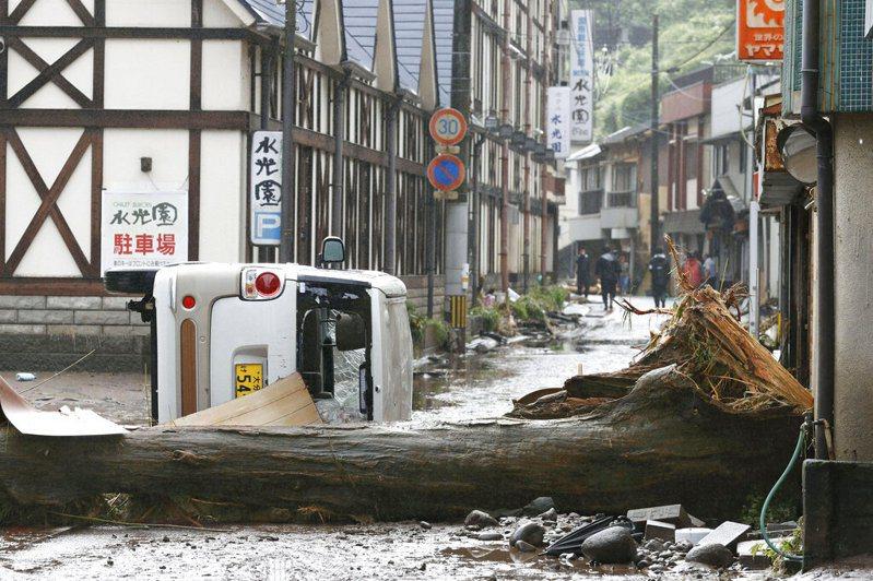 日本九州地方遭豪雨重創。圖為日本南部大分縣日田市,一場大雨過後,一輛汽車和一棵樹倒下了。 美聯社