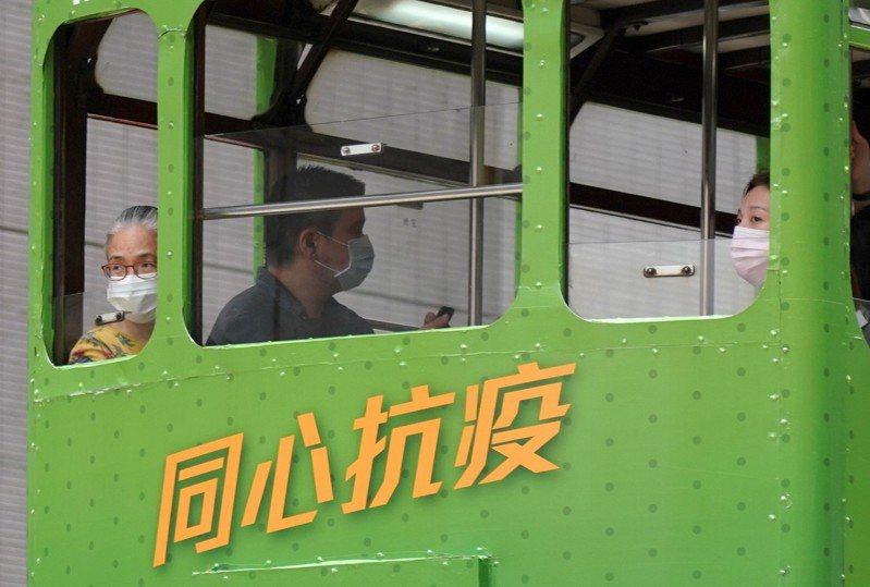 香港新冠肺炎疫情近日再度在社區爆發,今(9日)更大幅增加42例確診病例。圖為市民戴口罩搭電車出行,電車車身上張貼著「同心抗疫」公益廣告。 香港中國通訊社