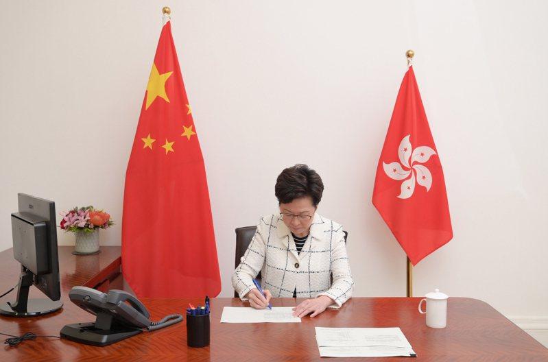 圖為林鄭6月30日簽署生效「港區國安法」。 中通社提供