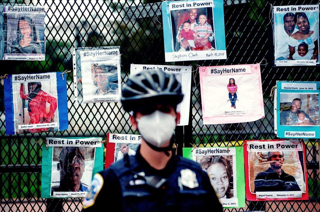 4日,白宮附近圍欄外,警察站在據示威者稱為警暴受害者的海報前。 圖/法新社