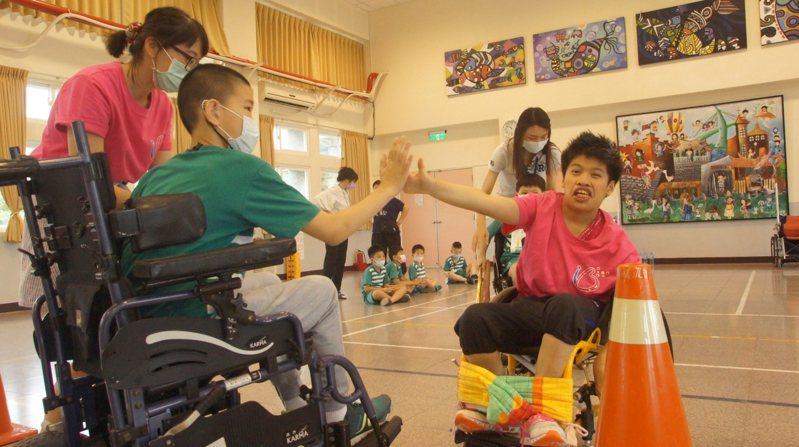小瑄(右)與淡水國小學生比賽輪椅競速,開心地互相擊掌。圖/八里愛心教養院提供