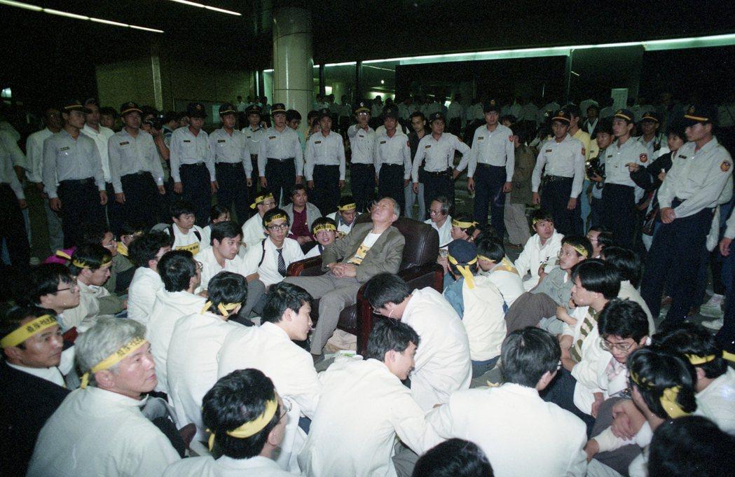 1991年10月10日凌晨,「一〇〇行動聯盟」成員於台灣大學醫學院等地靜坐抗議,警方開始將現場的靜坐人員抬上警備車載離,並查扣擴音器等器材,圖中為李鎮源。  圖/聯合報系資料照