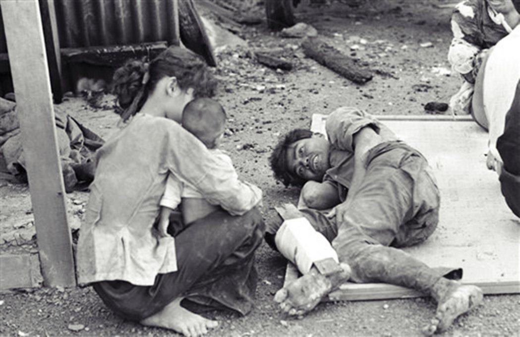 受傷的南越士兵1965年在急救站與家人團聚。 圖/美聯社