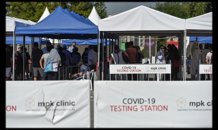 圖為哈薩克民眾在一處新冠病毒檢測點外排隊等候檢測。(路透)