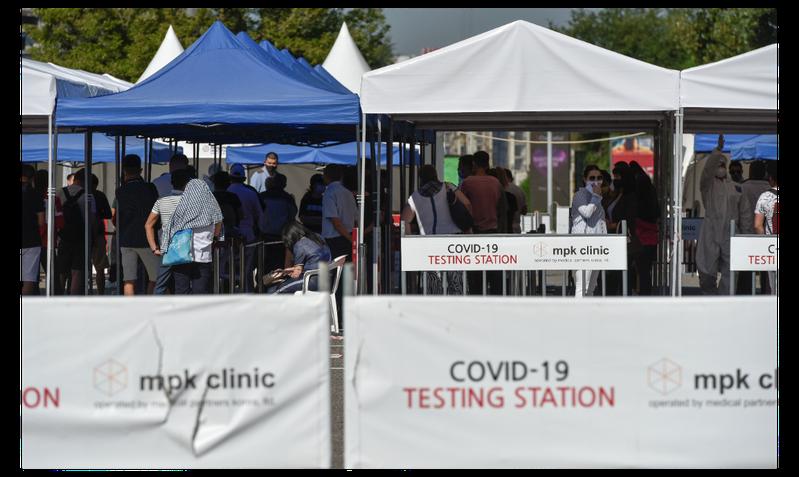 圖為哈薩克民眾8日在阿拉木圖一處新冠病毒檢測點外排隊等候檢測。(路透)