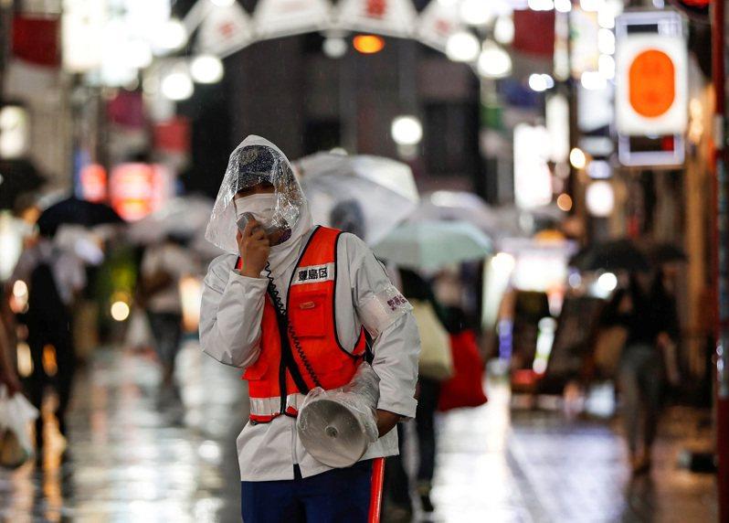 日本東京都豐島區一名工作人員9日晚間背著大聲公,在池袋街頭宣傳提醒防疫措施。路透