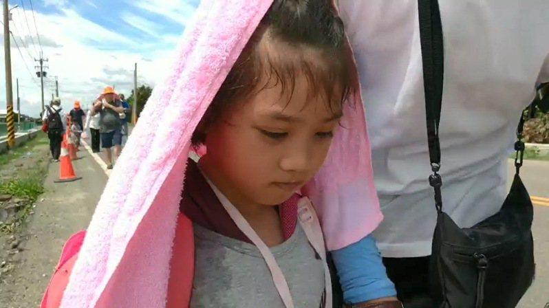 大太陽熱得刺人,羅小妹妹抱病隨香祈願,水喝乾了,由舅舅陪著一路勇敢往前走。記者蔡維斌/翻攝