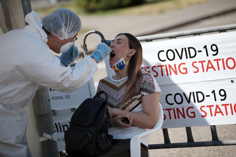 哈薩克醫務人員6月在阿拉木圖市為一名女子做新冠病毒檢測。(路透)
