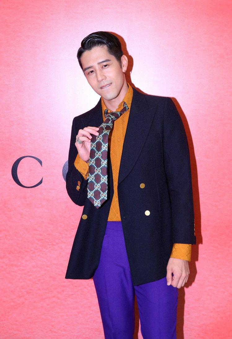 胡宇威穿排釦羊毛夾克87,000元、焦糖橘襯衫41,500元、丁香紫喇叭褲26,...