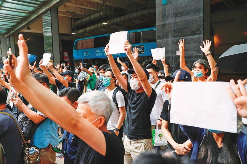 香港示威者赴東區法院聲援七一遊行被捕的群眾,為免觸犯港版國安法,他們手持空白的海報抗議。 (路透資料照片)