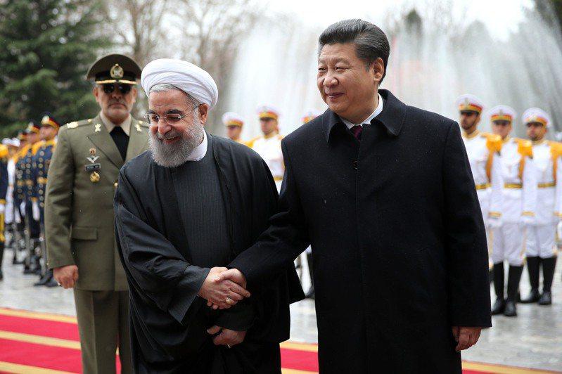 紐約時報報導,中國大陸與伊朗即將簽訂經濟及安全協議。圖為中國國家主席習近平(右)2016年1月23日訪問伊朗期間,伊朗總統羅哈尼在德黑蘭總統官邸薩德阿巴德宮舉行歡迎儀式。美聯社