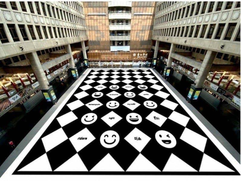 台鐵將北車大廳地板貼上多語言版本的微笑地貼。圖/取自林佳龍臉書