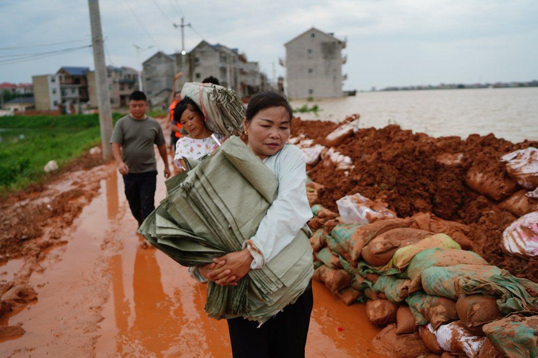 鄱陽縣江家嶺村村民幫忙搬沙袋,抵禦洪水。(新華社)