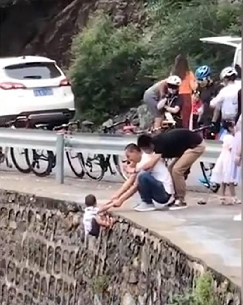 年約5歲的男童當日被一名男子捉着雙手吊在車道邊的懸崖外。圖/微博影片