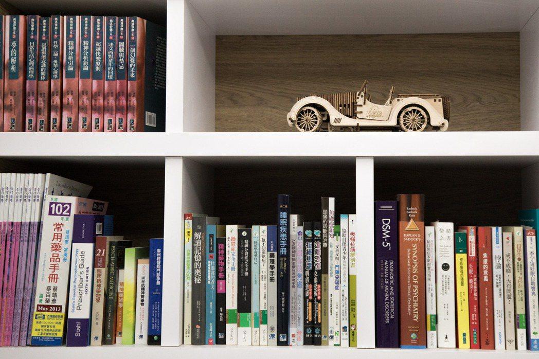 診所一隅,擺著各式精神科醫學書籍以及李俊人製作的木頭車模型。記者許詩愷/攝影