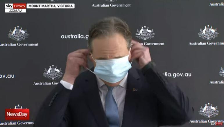 澳洲衛生部長杭特將左右兩側耳掛拉開,但口罩直接覆蓋眼睛,且耳掛彈開,沒有順利掛在耳朵上。圖翻攝自Youtube