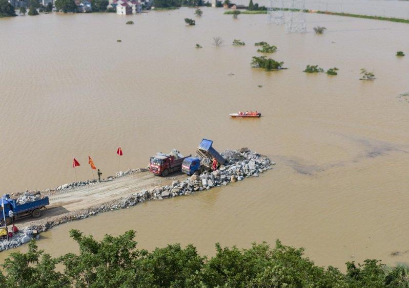 江西鄱陽河水不斷上漲,幾乎要漫過防水牆上沿。 圖/新華社