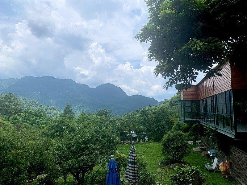 下方露營包場的綠地,在上方是餐廳和公共空間活動的客廳,往山的方向望過去山峰的景緻。