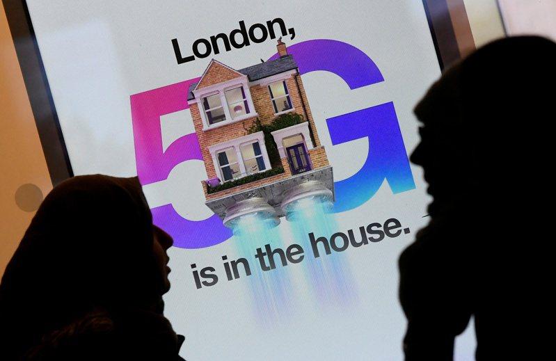 英国电信集团表示,10年内「无法」将华为的设备从英国基础设施中清除。 图为英国伦敦民众行经一个手机5G广告看板。 路透