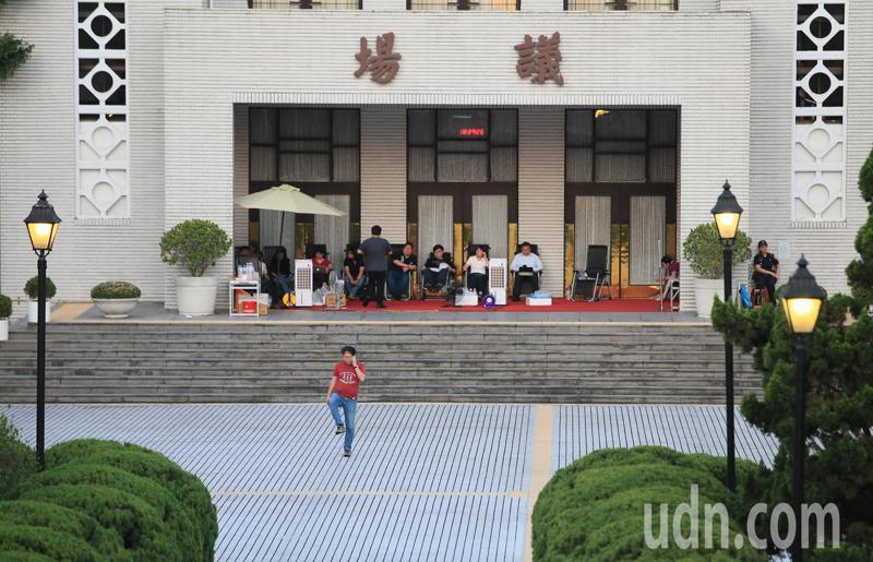 華燈初上,綠委搶先占據議場門口前排班。記者潘俊宏/攝影
